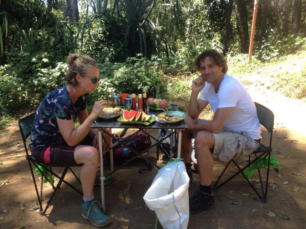 two people sat at a table eating a meal whilst on their rinjani hike